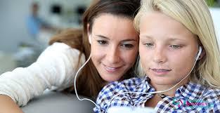2 girls listening to Apple headphones